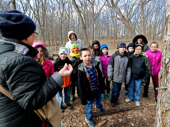 Jeanne Meyer, a volunteer naturalist at Wehr Nature Center in Whitnall Park, explains how maple tree producers make syrup to third-grade students from Good Shepherd's Evangelical Lutheran School.