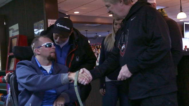 Josh Sommers, left, shakes the hand of Ken Webb during a surprise party for Sommers at Lexington Lanes on Saturday. Sommers served in the U.S. Army in Afghanistan, where he was injured in 2010 and was in a coma for eight months. He is undergoing rehabilitation.