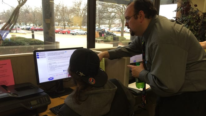 Michigan Department of Human Services case worker Matt Goff helps a person apply for the Healthy Michigan plan on April 1  in Lansing, Mich. The state expanded its Medicaid plan in order to provide health insurance for hundreds of thousands more low-income adults.
