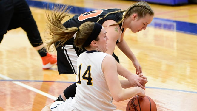 Woodmore's Lily Rothert, left, hounds Gibsonburg's Shylee Schmeltz for possession.