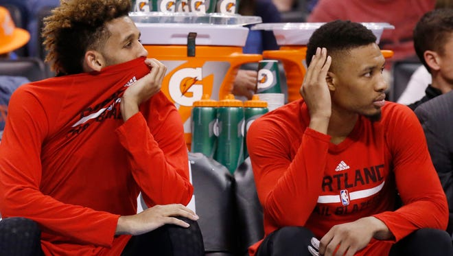 Portland Trail Blazers guard Allen Crabbe, left, and guard Damian Lillard, right, watch from the bench in the fourth quarter of an NBA basketball game against the Oklahoma City Thunder in Oklahoma City, Monday, March 14, 2016. Oklahoma City won 128-94.