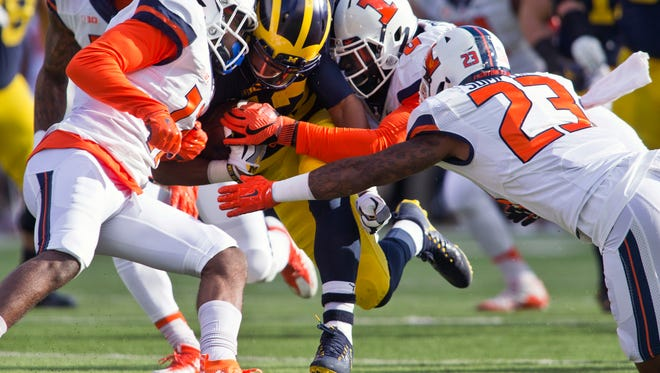 Michigan running back Chris Evans, center left, is hit from both sides by Illinois defensive back Stanley Green, front left, and defensive lineman Carroll Phillips, center right, in the first quarter Saturday at Michigan Stadium.