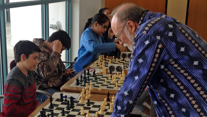 At left, Ayden Connolly, the youngest participant in the casual section of the 2016 Four Corners Open Chess Tournament, contemplates his move during the tournament earlier this month at San Juan College in Farmington. Scout Veitch, president of the New Mexico Chess Organization, is pictured at right.