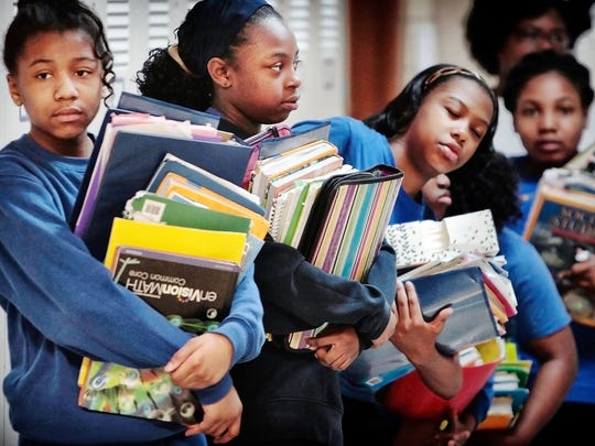 April 6, 2015 - Loaded down with a days worth of textbooks, Fifth graders wait to change classes Monday morning at St Augustine Catholic School. The Catholic Jubilee Schools are moving closer toward a year-round school calendar with classes starting again on July 27.