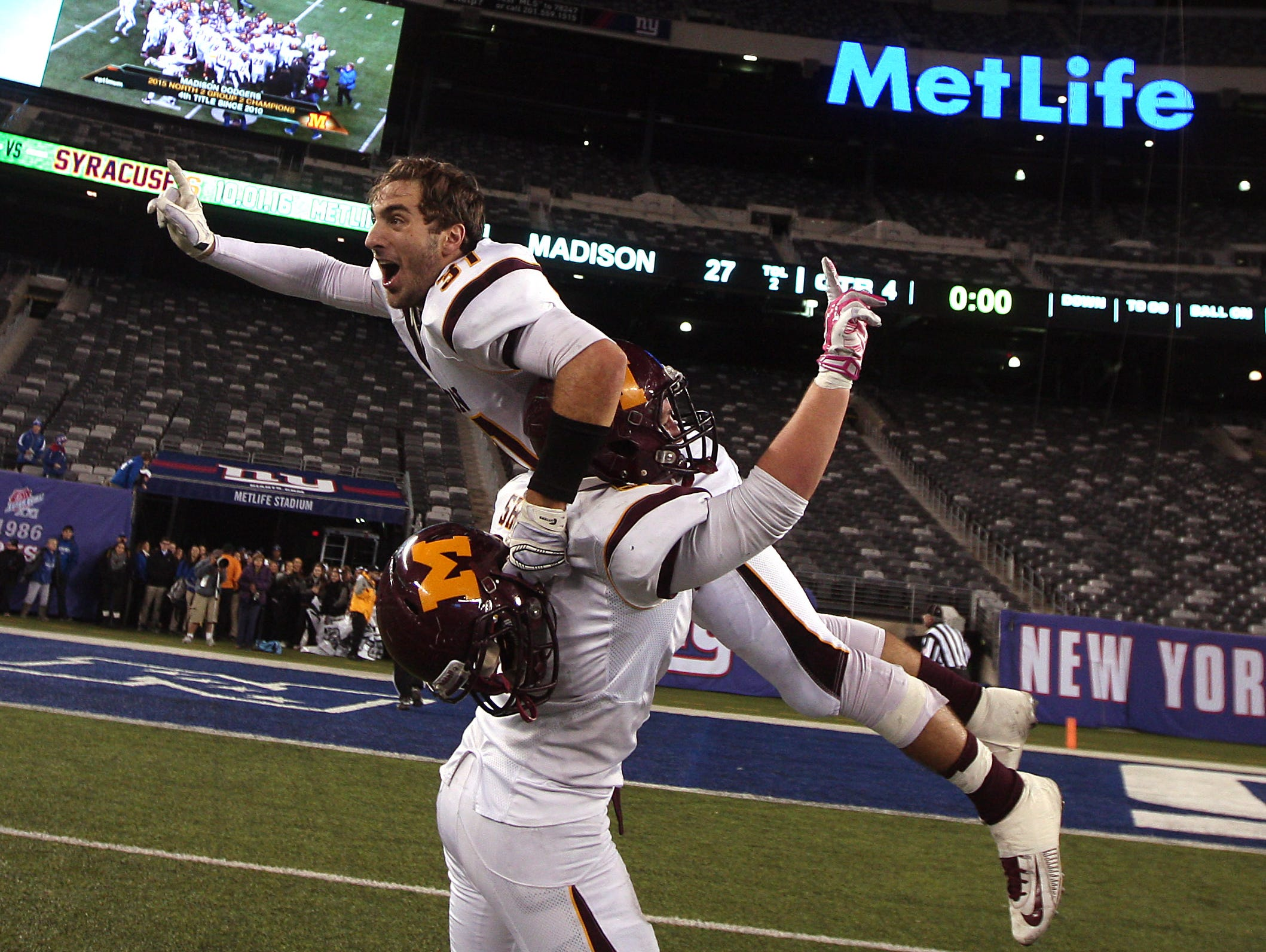 Madison's Zach Shupe lifts up teammate Justin Dalena after the Dodgers beat Rutherford in the North 2, Group 2 NJSIAA football Championship at MetLife Stadium. Madison won 27-6. December 3, 2015, East Rutherford, NJ.