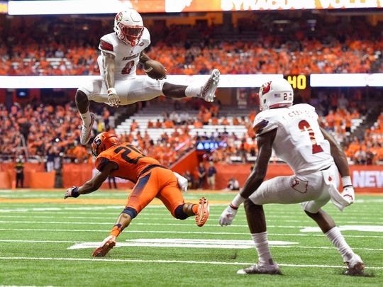 Louisville Cardinals quarterback Lamar Jackson (8) leaps over Syracuse Orange defensive back Cordell Hudson (20) during the second quarter at the Carrier Dome in Syracuse, N.Y. on Sept. 9, 2016.
