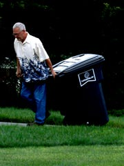 Curt Kraft pulls his newly delivered trash cart from the curb to his house Wednesday, June 27, 2018, in the River Valley Highlands neighborhood in Lancaster.
