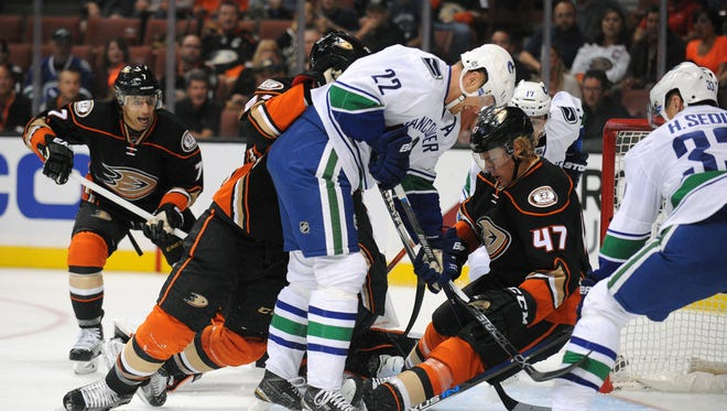 Anaheim Ducks defenseman Hampus Lindholm (47) helps defend the goal against Vancouver Canucks left wing Daniel Sedin (22) during the first period at Honda Center.