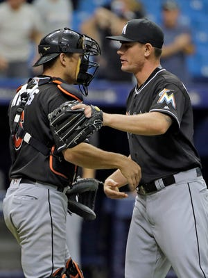 Miami Marlins relief pitcher Nick Wittgren, right, hugs catcher Jeff Mathis after closing out a 9-1 victory over the Tampa Bay Rays on Thursday.