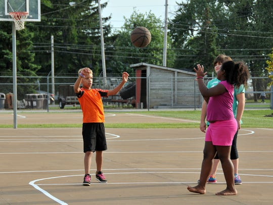 Children play basketball on the new courts at the West