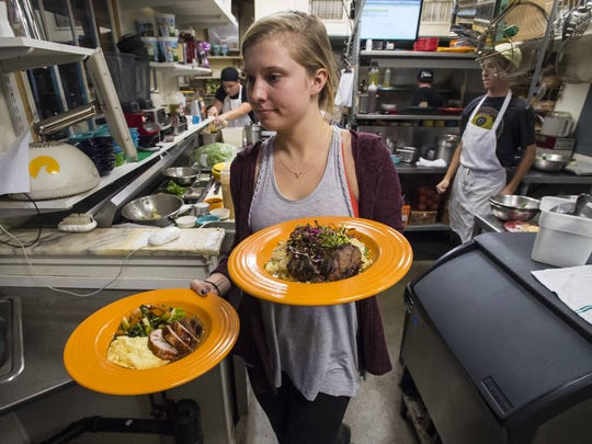 Parnell Kaffenberger takes dishes out to the dining