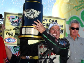 John Force talks with daughter Courtney Force during qualifying for the NHRA Nationals at Maple Grove Raceway.