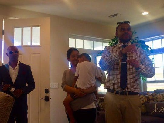 Zahid Ali surveys his new NextGen north Phoenix home with his wife and son after the big reveal Tuesday morning.