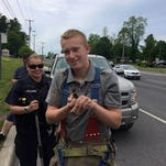 Firefighters work to rescue two ducklings caught below a storm drain Monday.