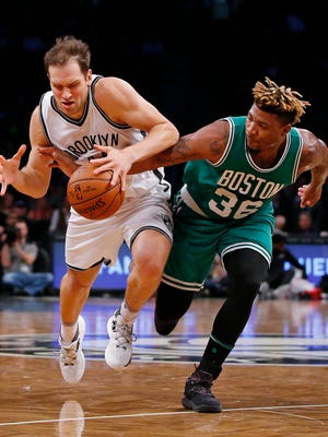 Brooklyn Nets guard Bojan Bogdanovic, left, fights off Boston Celtics guard Marcus Smart (36) as he attempts to keep possession of the ball during the first half  Wednesday, Nov. 23, 2016.
