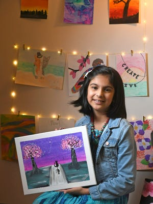 Advika Anand shows off her some of her artwork, June 3, 2020, at her home in Millcreek Township. Anand, 10, a fifth-grader at Grandview Elementary School, loves to paint and has been building a body of completed work.