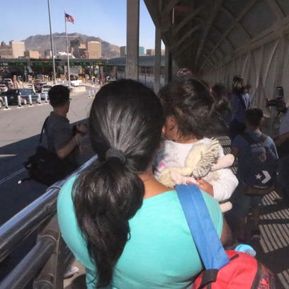 An asylum seeker from Mexico is led to the U.S. Paso