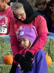 "Olea Ortiz, 8, is kept warm on a 37-degree Thanksgiving morning prior to the start of the 14th annual Ultimate Fitness Turkey Trot at Voiers' ""Pit"" Park."