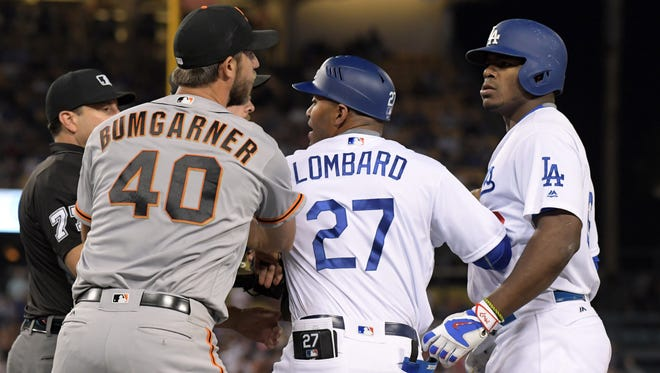 Madison Bumgarner and Yasiel Puig are restrained by Dodgers first base coach George Lomgard.
