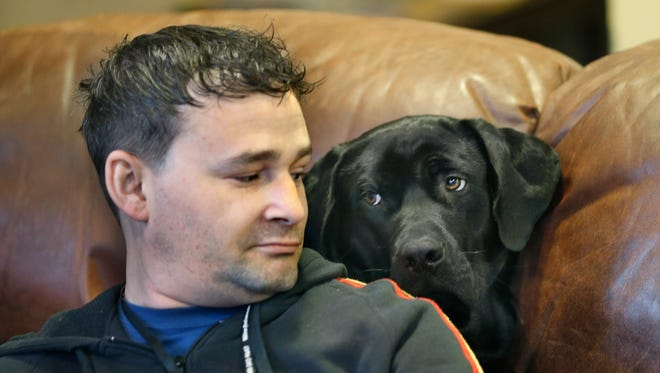 Army veteran specialist Joshua Wichtman, 33, is sized up by Hans, a black Lab mix puppy at the Veteran Outreach Center's Richards House.
