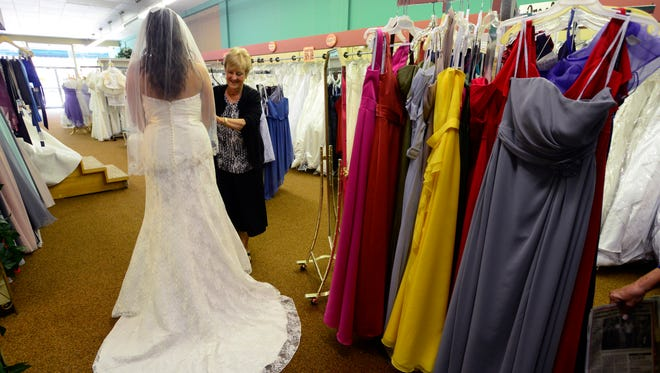 Barb Moran-Engler, co-owner of A Personal D'Signs bridal store, helps a bride-to-be try on wedding gowns.