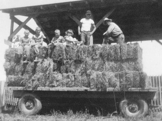 The Bodensteiner family stacks hay on its farm in rural Jackson County, Iowa, in the 1950s.