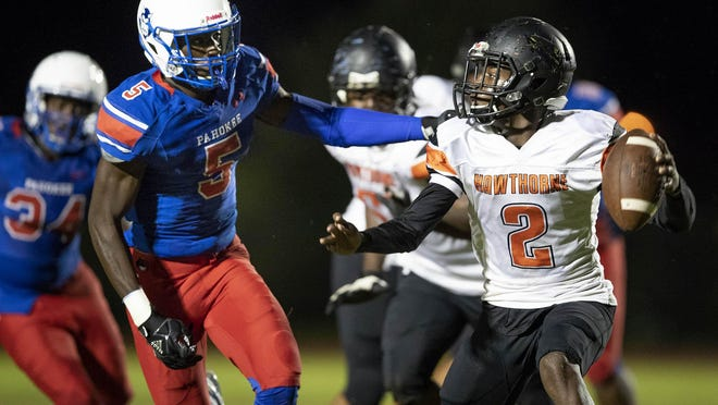 Pahokee Blue Devils defensive end Frankie Burgess (5) pressures Hawthorne Hornets quarterback Key'shaun Williams (2) to throw an incompletion in the first quarter in Pahokee, Nov. 15, 2019. Burgess is the 2020 Best of Preps Male Athlete of the Year.