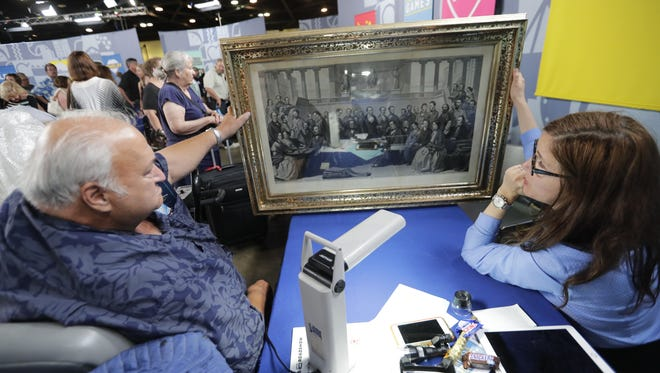 """Antiques Roadshow"" art expert Laura Ten Eyck of Argosy Gallery in New York City evaluates a 19th century engraving of American authors owned by Karl S. of Chicago when the PBS show visited the Resch Center in Ashwaubenon in June."