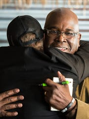 Christopher Behney (left) founder of the original Just Wing It, hugs Ricky Bugg Sr., father of Ricky Bugg Jr., during a press conference at the Annville Just Wing It on Monday, Jan. 30, 2017 to tell their side of the story after Behney was accused of directing a racial slur toward Bugg Jr., a Lebanon Valley College, student early morning on Jan. 22, 2017.