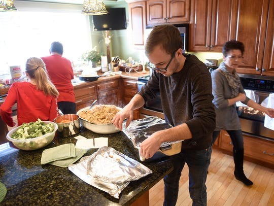 Family members fill the kitchen of the Gorecki Guest House while preparing a traditional Christmas dinner Monday, Dec. 25, in St. Cloud.