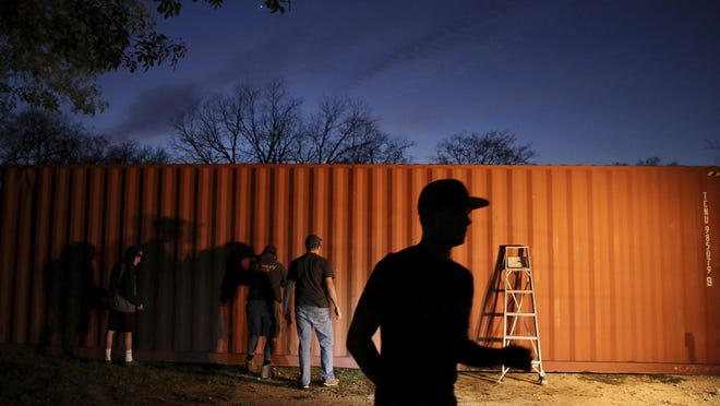 "A group of teenagers from The Church of Jesus Christ of Latter Day Saints and Boy Scout Troop 1042 paint a shipping container that will become a house for a homeless veteran when it is completed in Montgomery, Texas. This was the first ""tiny house"" that the Montgomery-based nonprofit Green Zone Housing started and hoped to continue."