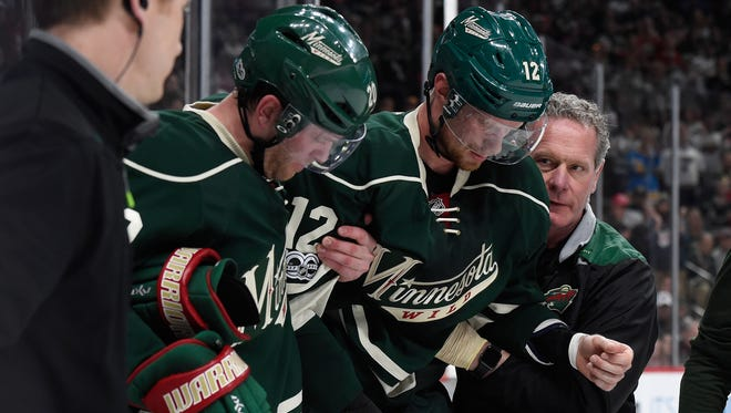 Minnesota Wild center Eric Staal is helped off the ice after crashing face-first into the boards.