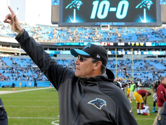 FILE - In this Nov. 22, 2015, file photo, Carolina Panthers head coach Ron Rivera points to his wife in the stands after an NFL football game against the Washington Redskins, in Charlotte, N.C.  Panthers coach Ron Rivera was on the hot seat a few years ago, but owner Jerry Richardson showed patience and helped guide Rivera through some growing pains. Now, in Year 5, Rivera's Panthers are 15-1 entering Sunday's divisional playoff game against Seattle. (AP Photo/Mike McCarn, File)