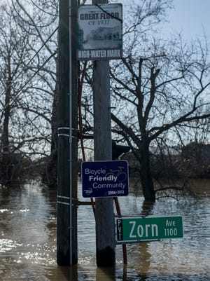 "A sign marks the height of the 1937 ""Great Flood"" along River Road in Louisville, Kentucky after weekend flooding crested the Ohio River's waters Monday. Feb. 26, 2018"
