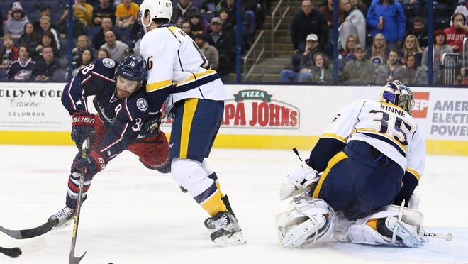 Blue Jackets center Boone Jenner (38) scores against Predators goalie Pekka Rinne (35) as he is checked by defenseman Shea Weber (6) in the second period Friday.