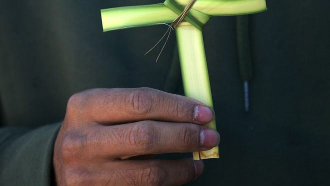 A St. Pius X parishioner fashioned a cross from a palm frond during a past Palm Sunday.