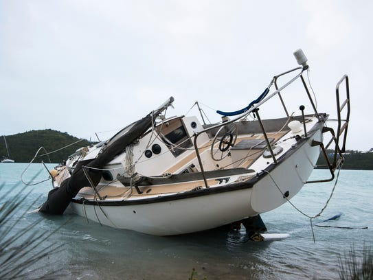 A sailboat lays damaged on the shore of Ferry Reach