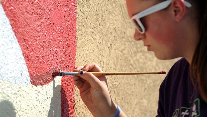 Taylor Jordan, a student at Millersport High School, paints a part of a mural Tuesday, Aug. 30, 2016, in Millersport. Jordan and other members of the school's art club are painting the mural on the village's police station.