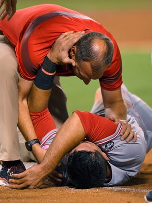 The Cincinnati Reds' Jose Peraza, below, is attended to by a trainer after being hit in the head with a ball thrown by Los Angeles Angels starting pitcher Matt Shoemaker while trying to dive back to first during the third inning of a baseball game, Monday, Aug. 29, 2016, in Anaheim, Calif.