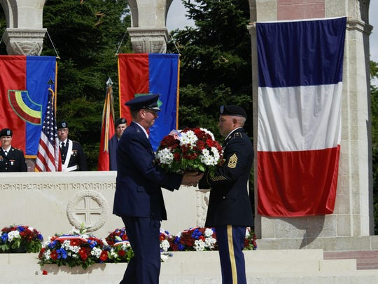 1st Sgt Seth Wilkinson, Vermont National Guard, hands a wreath to Gen. Joseph Lengyel, chief National Guard Bureau, during a ceremony at the Oise-Aisne American Cemetery honoring fallen French and American forces from the Great War.