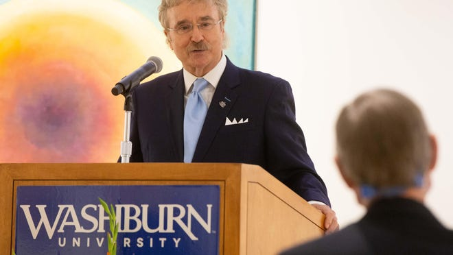 Michael Manning, a Washburn University School of Law alumnus and accomplished trial lawyer, praises university president Jerry Farley after the university recognized Manning's storied career as a trial attorney and his $1 million donation for a new law school building.
