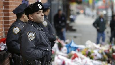 New York City police officers watch over a makeshift memorial Monday near the site where fellow officers Rafael Ramos and Wenjian Liu were murdered in Brooklyn