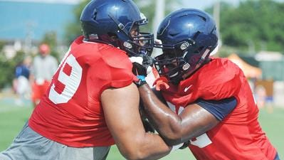 Offensive guard Javon Patterson (left) and Aaron Morris go through a drill. Patterson figures to be Ole Miss' starting left guard this fall, taking over for Morris.
