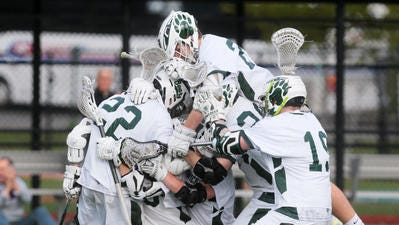 East Brunswick's Timmy Smith (22) celebrates with teammates after scoring the overtime goal to beat South Brunswick 11-10 in overtime in the GMC Tournament quarterfinals on May 10, 2016.
