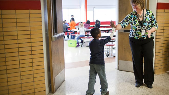 Stephanie Wassom, from Women's Life Insurance Society, smiles and claps hands with her lunch buddy, Zion Berry, 6, as they meet outside the lunch room Feb. 18, 2015 at Woodrow Wilson Elementary School in Port Huron. The Lunch Buddies program pairs up students with adults from the community.