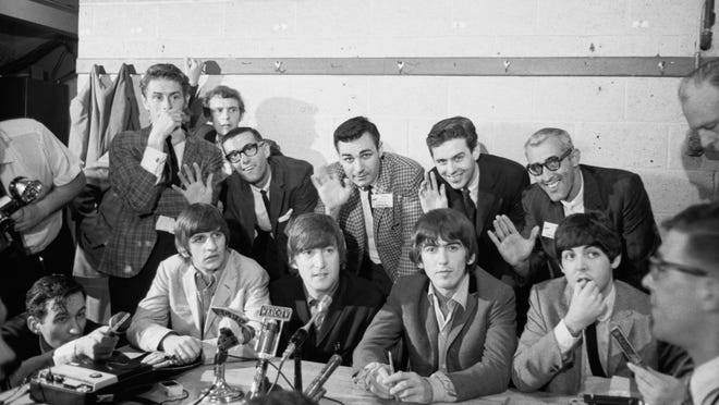 Dusty Rhodes (back row, second from right) and fellow WSAI-AM DJs wave to Walt Burton's camera while standing behind the Beatles during the band's Cincinnati Gardens' press conference in 1964.