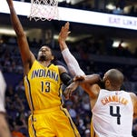 Indiana Pacers' Paul George (13) drives past Phoenix Suns' Tyson Chandler (4) for a score during the first half of an NBA basketball game, Tuesday, Jan. 19, 2016, in Phoenix. (AP Photo/Ross D. Franklin)