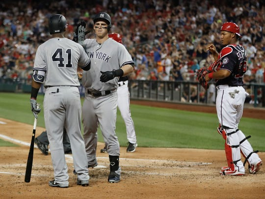 New York Yankees' Tyler Austin (26) is greeted by teammate Miguel Andujar (41) after hitting a two-run home run off Washington Nationals Gio Gonzalez during the fourth inning of an interleague baseball game against the New York Yankees at Nationals Park, Tuesday, May 15, 2018, in Washington. Looking on is Washington Nationals catcher Pedro Severino (29).