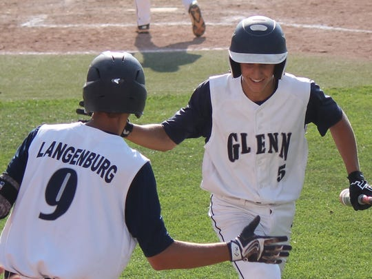 Corey Langenburg congratulates pinch-runner Blake Waibel after scoring a run in Bay City John Glenn's 15-4 rout of Dearborn Divine Child on June 15, 2017.