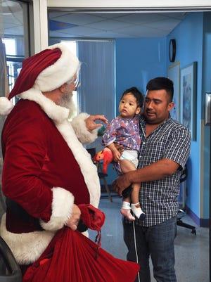 """Santa"" Dan Sutter greets baby Jadiel and his dad, Rogelio Jimenez, who were spending Christmas at Golisano Children's Hospital."
